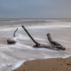 long exposure of sticks laying on the beach at Covehith