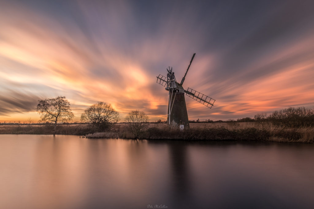 How hill on the Norfolk broads during a photography workshop at sunset with a fire red sky and refelction on the water