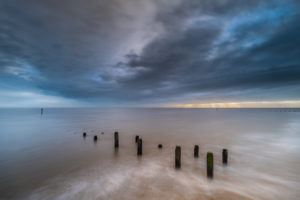 long exposure sunrise at overstrand on the Norfolk coast with blue sky and smooth water