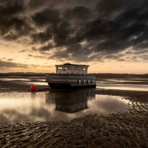 Morston boat at sunrise with its refection in the water