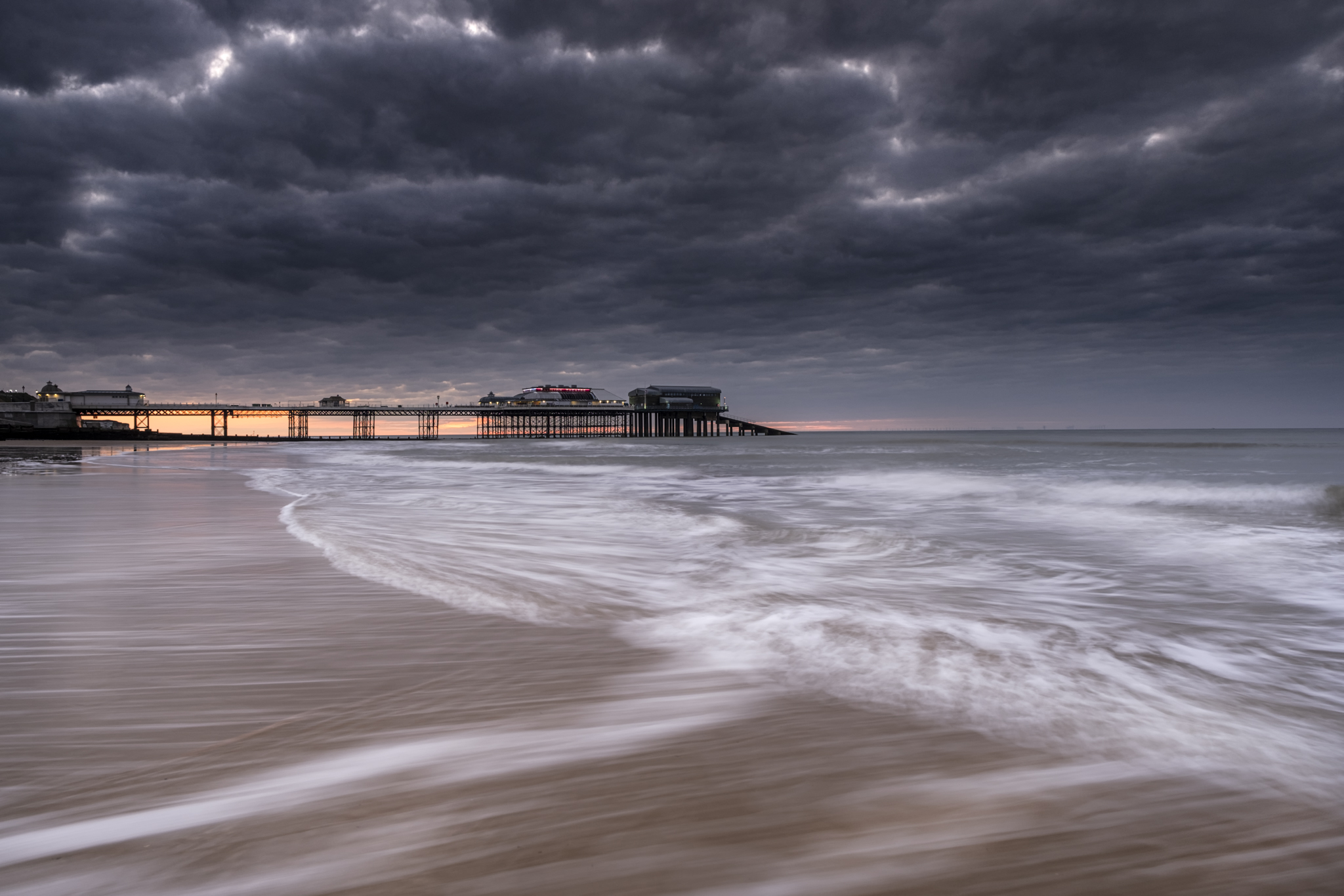 cromer pier on the Norfolk coast with the waves crashing on the beach